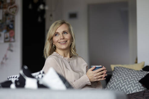 Smiling blond woman relaxing at home sitting on couch - RBF07055