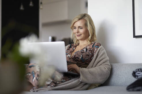 Blond woman using laptop on couch at home - RBF07058