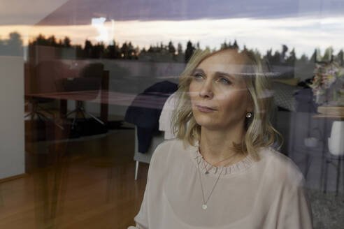 Portrait of blond woman behind windowpane at home - RBF07064