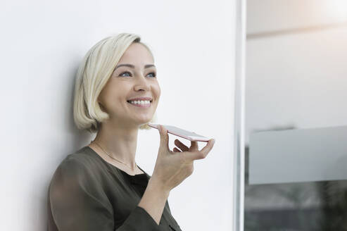 Portrait of smiling businesswoman using mobile phone - BMOF00168