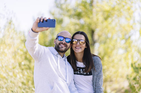 Couple wearing sunglasses and taking a selfie in a park - DGOF00436