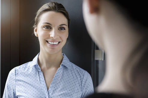 Portrait of smiling businesswoman meeting colleague in office - BMOF00188