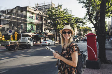 Smiling woman standing with map at a street, Bangkok, Thailand - CHPF00641