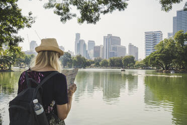 Rear view of woman looking at map in Lumphini Park, Bangkok, Thailand - CHPF00644