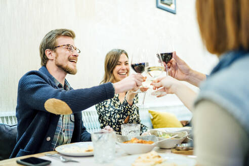 Friends dining in an Indian restaurant, toasting wine glasses - OCMF01035