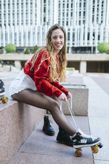 Portrait of happy young woman putting on roller skates in the city - KIJF02898