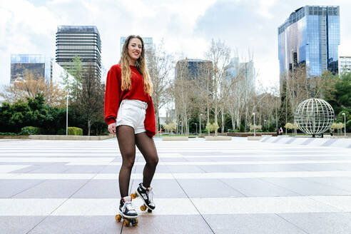 Portrait of happy young woman roller skating in the city - KIJF02904
