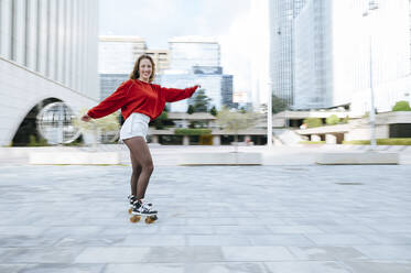 Portrait of happy young woman roller skating in the city - KIJF02907