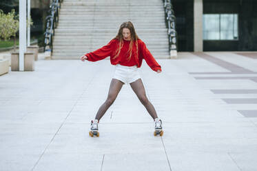 Young woman roller skating in the city - KIJF02913