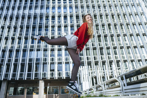 Happy young woman balancing on roller skates in the city - KIJF02916