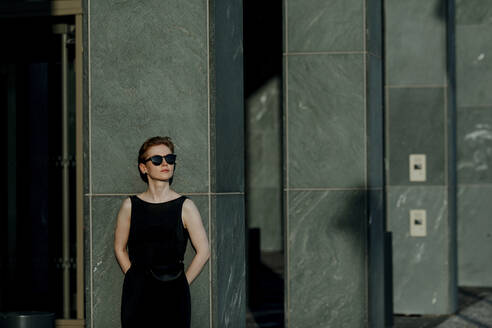 Red-haired woman with sunglasses, leaning on pillars in the city - OGF00138