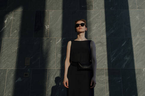 Red-haired woman with sunglasses, in front of stone wall with shadows - OGF00141