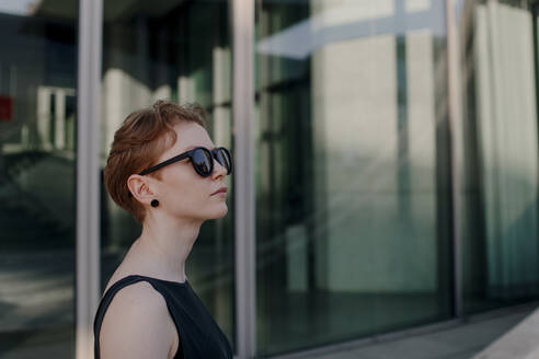 Elegant red-haired woman with sunglasses in the city, portrait - OGF00144
