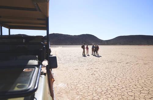Safari tour group walking in sunny arid desert South Africa - CAIF23996