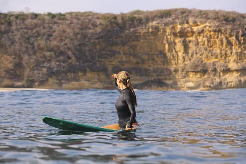 Happy woman sitting on surfboard in sea - CAVF74876