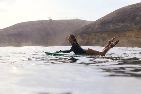 Happy woman sitting on surfboard in sea - CAVF74879