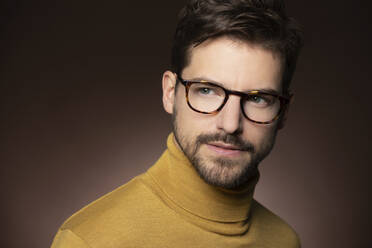 Portrait of confident man wearing glasses and yellow sweater - SHKF00814