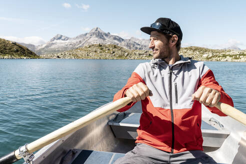 Young smiling man in a rowing boat, Lake Suretta, Graubuenden, Switzerland - HBIF00036