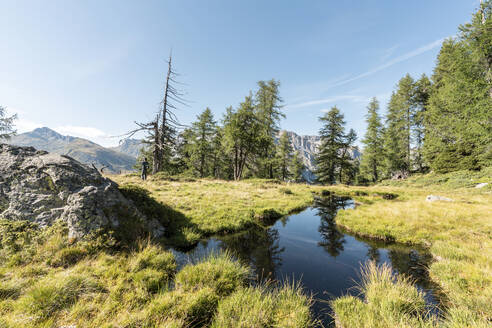 Pond and hiker in the background, Alps, Graubuenden, Switerland - HBIF00042