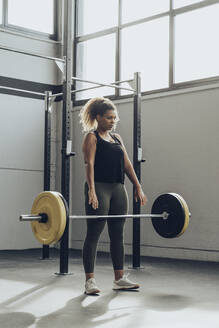 Young woman weightlifting in gym - MTBF00343