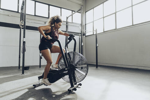 Young woman doing air bike workout in gym - MTBF00346