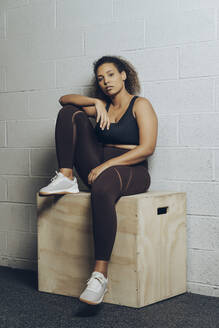 Portrait of confident athletic young woman sitting on a box - MTBF00352