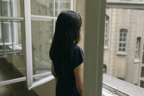 Back view of woman looking out of window - OGF00146