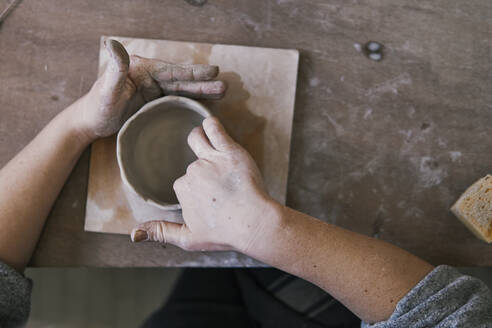 Close-up of potter working on workpiece - JPIF00315