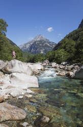 Man standing on rock at Verzasca river, Verzasca Valley, Ticino, Switzerland - GWF06457
