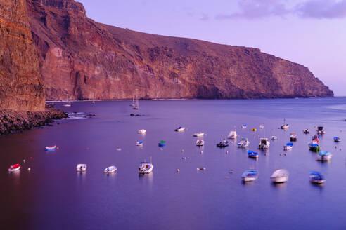 Spain, La Gomera, Valle Gran Rey, Boats moored in front of coastal cliff at purple dusk - SIEF09555