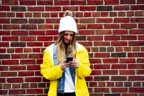Attractive blonde woman using a smartphone on a brick wall - CAVF75049