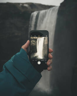 Cropped hand photographing waterfall in Iceland with smartphone - CAVF75061