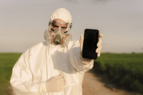 Man wearing protective suit and mask in the countryside holding cell phone - ERRF02628