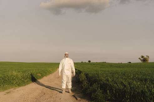 Man wearing protective suit and mask in the countryside - ERRF02631