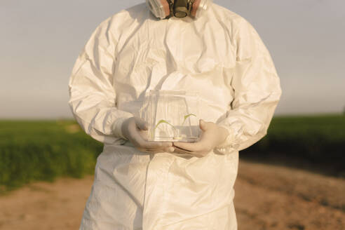 Man wearing protective suit in the countryside holding seedling in glass case - ERRF02637
