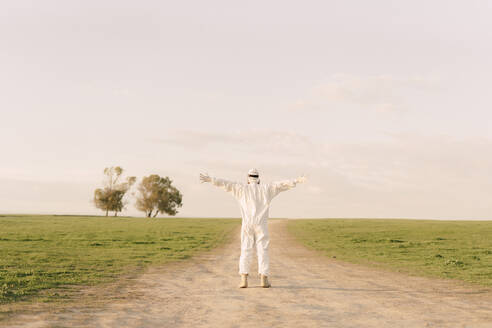 Rear view of man wearing protective suit standing on dirt track in the countryside - ERRF02643
