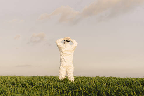 Rear view of man wearing protective suit in the countryside - ERRF02652