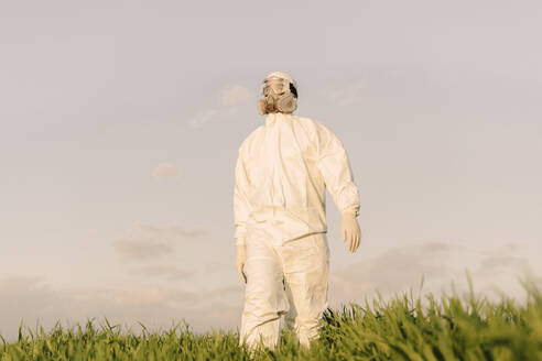 Man wearing protective suit and mask in a field - ERRF02655