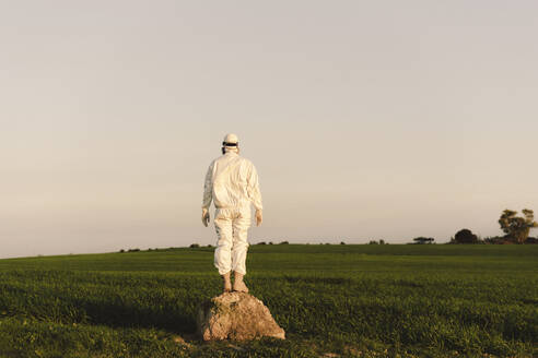 Man wearing protective suit and mask standing on a rock in the countryside - ERRF02664