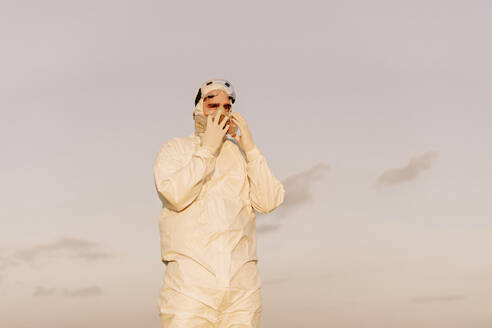 Man wearing protective suit and mask in the countryside - ERRF02667