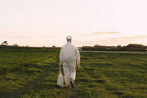 Rear view of man wearing protective suit walking in the countryside - ERRF02676