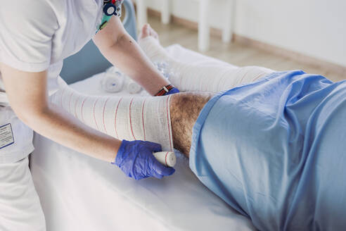 Nurse wrapping bandage around patient's leg in hospital bed - LJF01353