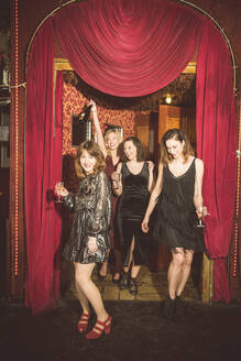 Four happy women entering a club - HBIF00043