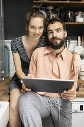 Young couple sitting on kitchen worktop, using digital tablet - PESF01809