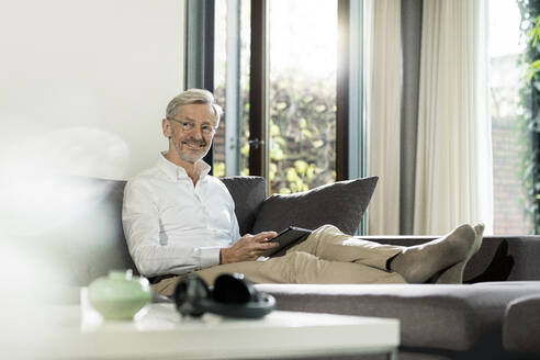Smiling senior man with grey hair in modern design living room sitting on couch holding tablet - SBOF02103