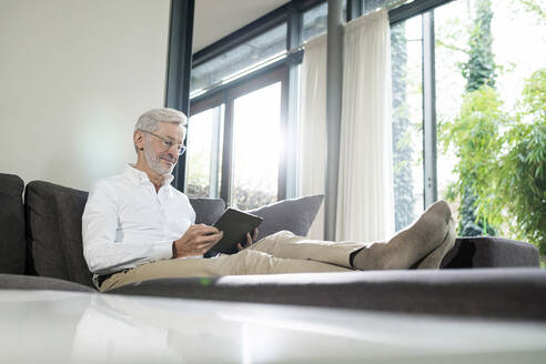 Senior man with grey hair in modern design living room sitting on couch using tablet - SBOF02106