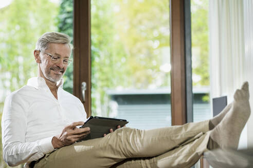 Smiling senior man with grey hair in modern design living room sitting on couch using - SBOF02109