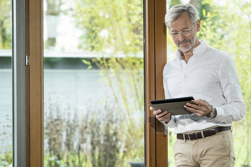 Senior man with grey hair in modern design living room standing at window using tablet - SBOF02112