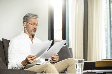 Senior man with grey hair in modern design living room sitting on couch working on papers in home office - SBOF02115