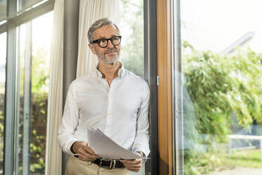 Senior man with grey hair in modern design living room standing at window holding papers in home office - SBOF02118